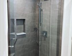 Walk-in shower; Soap niche with metal edging; Thermostatic controlled shower set with sliding bar for hand-held head; Wall-mounted rain head; LED potlight shower