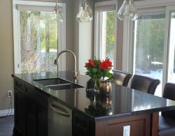 Contrasting island in rich, dark brown wood finish, with granite top, provides additional work and storage space