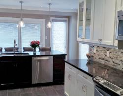 Galley-style kitchen with island provides more open flow, increased work space and more storage than pre-existing peninsula and free-standing stable, contemporary glass/stone-combination strip-style elongated backsplash. Contrasting island in rich, dark brown wood finish accents white cabinetry.