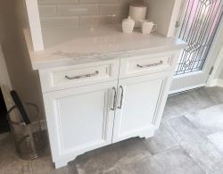 Transitional Chalet pulls in brushed-satin nickel finish; Hereford doors in Frost White