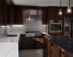 Wall-mount stainless steel hood, chimney style; Book-matched vertical-grain, natural-walnut cabinetry, Cuisine Ideale York door style