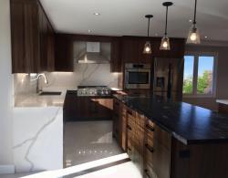 Kestle Interiors, Quartz waterfall countertop in Callacatta Nature; Book-matched vertical-grain, natural-walnut cabinetry, Cuisine Ideale York door style