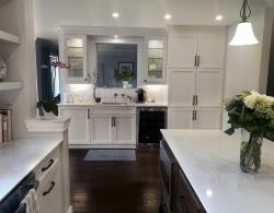 Bar area with pass-through; glass-front upper cabinets, bottom cabinets with sliders, extra deep bottom; pantry unit with pull-outs