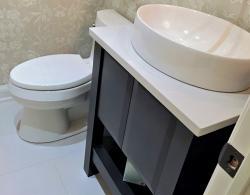 Kohler oval vessel sink; Charcoal-coloured vanity with pillow door style, open shelf unit; Kestle Interiors Newmarket Powder Room Design