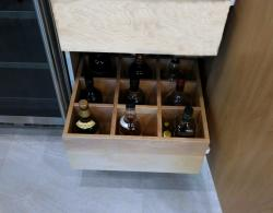 Pull-out, solid wood drawers with compartments for bottles/vases; door interior, simulated natural maple melamine, to match drawers