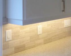 """Quartz countertop, 2"""" x 4"""" porcelain-tile backsplash with under-cabinet task lighting."""
