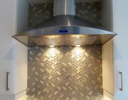 Featuring a beautiful glass-mosiac tile backsplash behind the range