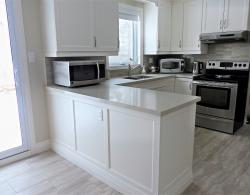 Pearl White lacquer finished cabinetry; Quartz countertop