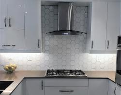 Stainless-steel chimney hood; Full-height backsplash in hex porcelain tiles